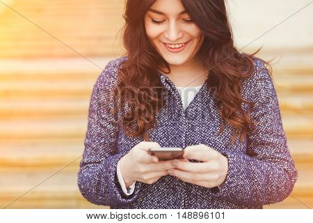 Closeup caucasian woman female using cellphone smartphone walking while texting. Brunette girl wearing a coat smiling and using map app to navigate on city streets