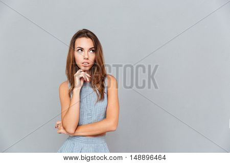 Pensive beautiful yougn woman standing and thinking over grey background