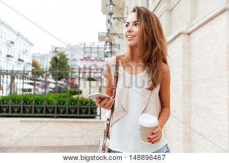Smiling beautiful girl walking on the street and drinking take away coffee
