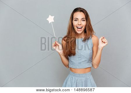 Happy amazed young woman holding magic wand over grey background