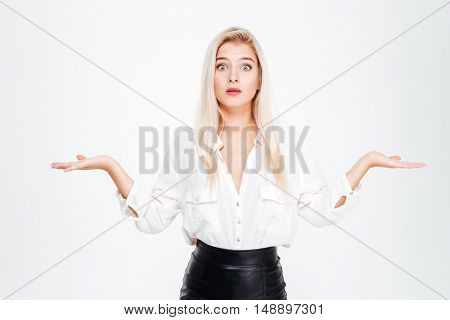 Confused thoughtful young businesswoman holding copyspace on both palms over white background