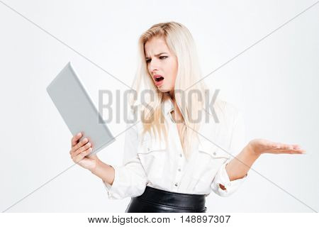 Surprised young businesswoman looking at tablet computer isolated on a white background