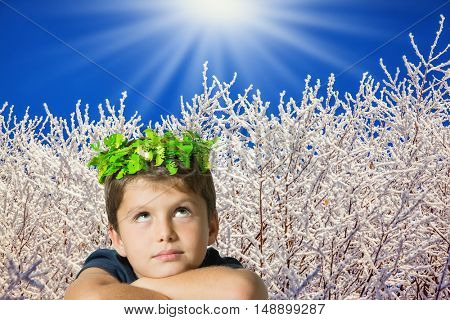 Charming seven year old boy in carnival wreath of green leaves. Background of winter forest
