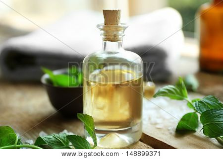 Bottle with mint oil and fresh leaves on wooden table