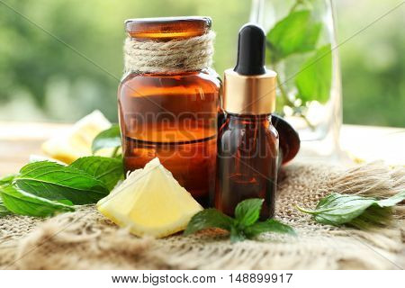 Bottles with mint oil, lime and fresh leaves on table, blurred natural background