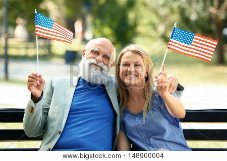 Granddaughter and her grandfather with American flags in a park
