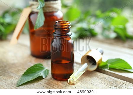 Bottles with mint oil and fresh leaves on wooden background