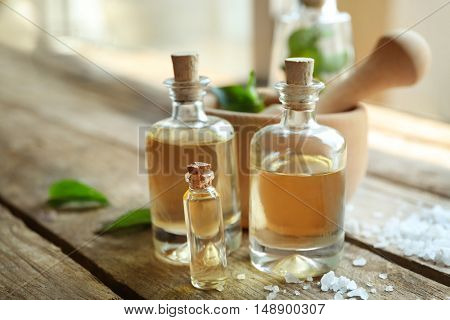 Bottles with mint oil and fresh leaves on wooden table