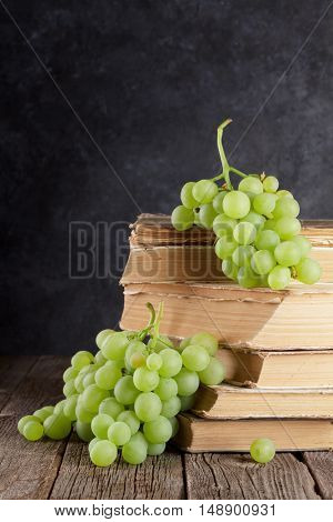 White grapes over old books on table in front of stone wall with copy space