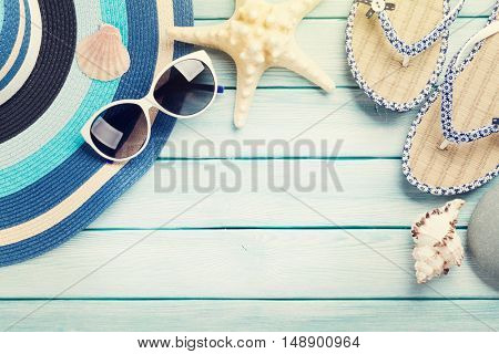 Beach accessories. Flip flops, sunglasses and starfish on wooden background. Top view with copy space. With sun beam