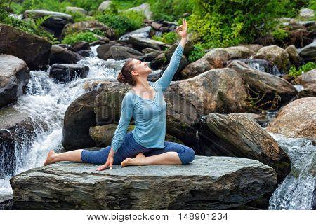Yoga outdoors - young sporty fit woman doing stretching yoga asana Eka pada rajakapotasana - one-legged king pigeon pose at tropical waterfall