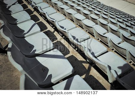 Top shot of empty light blue plastic stadium seats with harsh shadows
