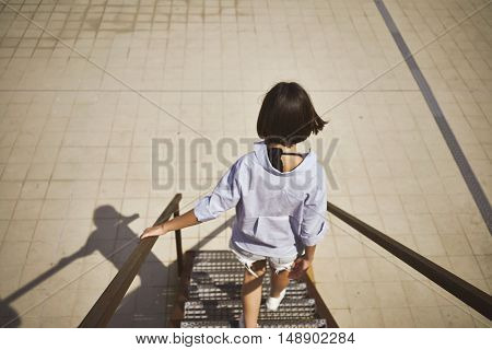 Unfocused back shot of a beautiful thin young woman wearing a light blue shirt with dark hair walking down a metal staircase on a summer day.