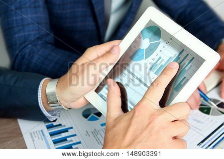 Business colleagues working and analyzing financial figures on a digital tablet
