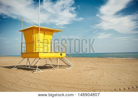 Flowy white clouds above a sunlit yellow lifeguard post on an empty sandy beach near quiet sea