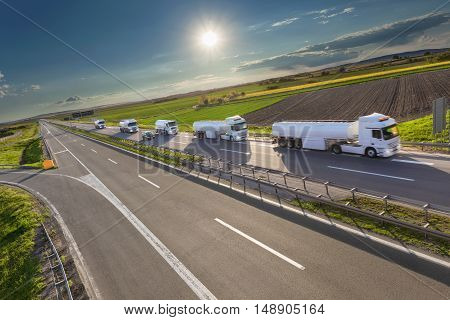 Many white gasoline tanker trucks in a row driving towards the sun. Fast delivery on the freeway at beautiful idyllic day. Freight scene on the motorway near Belgrade Serbia.
