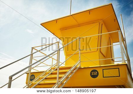 Newly painted yellow lifeguard booth with closed windows shot from the ground