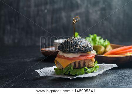 Homemade black burger with grilled chicken patty on dark background
