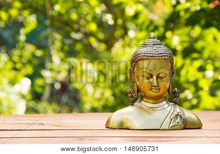 Buddha statue on natural blur green background. Spa concept. Calmness and tranquility. Copy space. Statuette of brass. Golden statuette.