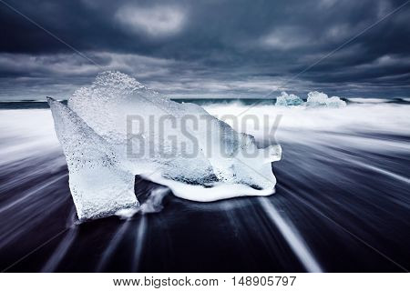 Great view of the ice fragments on black sand. Popular tourist attraction. Dramatic and picturesque scene. Location place Vatnajokull national park, Jokulsarlon lagoon, Iceland, Europe. Beauty world.