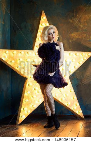 Beautiful playful adult blonde woman wearing dark blue lace tutu skirt and mesh stockings posing over dark background with glowing star. Actress playing on stage. Theatre or dancer.
