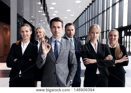 Portrait of successful business man showing ok sign with his team