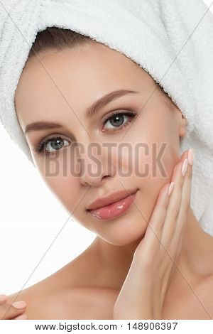 Portrait Of Young Beautiful Woman With Towel On Her Hair Touching Her Face