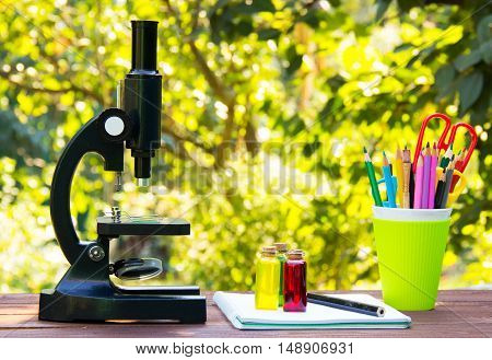 Microscope and stationery on wooden table. Glass flasks with colored liquids Natural green blur background. School concept. Copy space