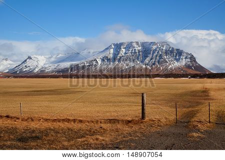 Grundafjördur Icelandic Mountain in Winter covered in snow with a field in the foreground on a sunny day