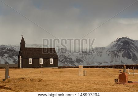 Black Church of Budir in Iceland at daytime with clouds and sunlight