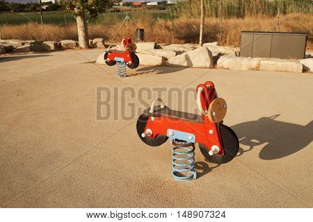 Toy seesaw motorcycles in a playground on a warm summer evening