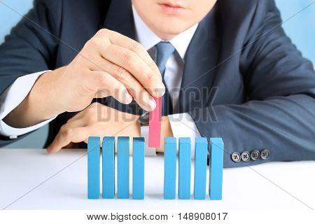 Planning risk and strategy in business businessman putting down wooden block
