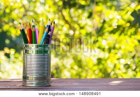 Colored pencils in a tin can on a wooden table. Natural green background. Green blur. Copy space. School concept.