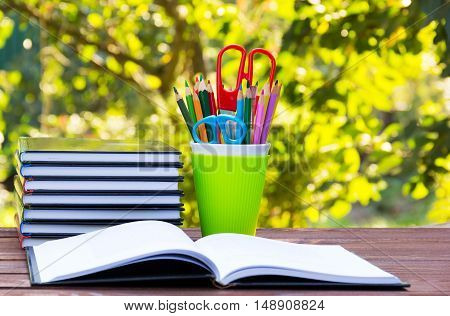 A stack of book and a glass with colored pencils. A set of stationery items in green glass. An open book on a wooden table. School concept. Copy space.
