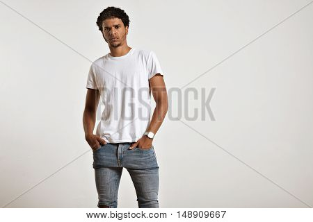 Serious athletic young African American model with hands in the pockets of his tight blue jeans wearing a white t-shirt