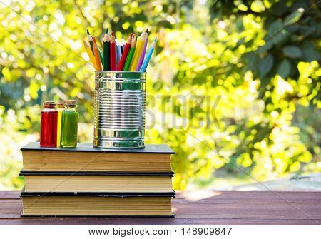 A stack of old textbooks, colored pencils in a tin can and flasks with the ingredients. Homework. School concept.