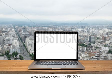 Laptop with blank screen on table. with Kyoto Japan backgraund