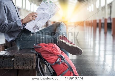 Side portrait of a young man traveler sitting with map choose where to travel and bag waiting for train at train station.