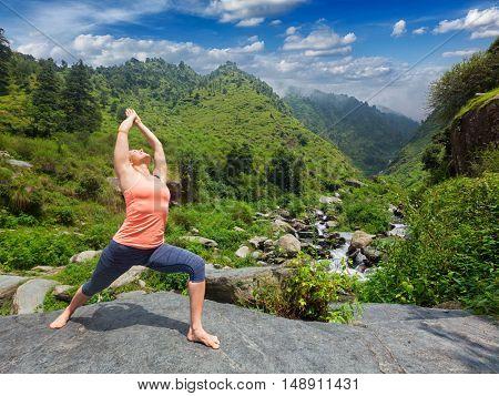 Yoga outdoors - sporty fit woman doing Ashtanga Vinyasa Yoga asana Virabhadrasana 1 Warrior pose posture at waterfall in HImalayas mountains
