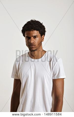 Gloomy young black model in clean white unlabeled cotton t-shirt looking into the camera
