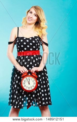 Management time concept. Blonde fashion girl wearing black dotted dress smiling face expression with alarm clock on blue.