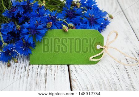 paper tag with cornflowers on a old wooden table