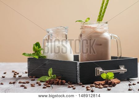 Iced coffee with milk in glass jur on wooden table decorated with cinnamon and mint