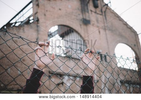 Refugee two hands keeping metal fence mesh