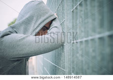 Lonely sad Man Leaning against a Fence