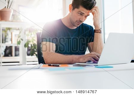 Shot of young man using laptop and looking worried. Businessman working at his desk.