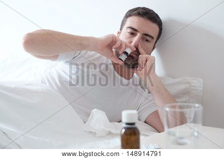 Man Feeling Cold And Using A Nasal Spray Lying In The Bed