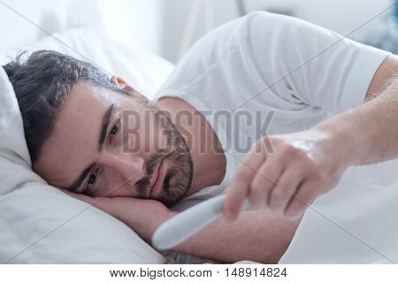 Man Feeling Bad Lying In The Bed And Looking The Thermometer