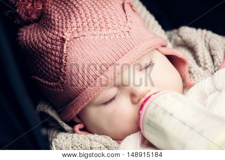 Baby drinking milk from the bottle with her eyes closed. Close-up portrait
