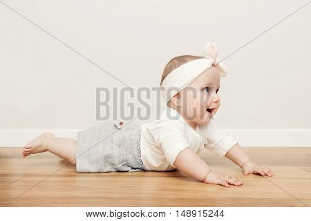 Cute happy baby crawl on wooden floor wearing funny headband. Vintage